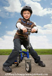 Happy smiling young asian boy on his bike looking at the camera and wearing a helmet